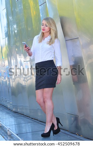 Young businesswpman checking messages on her smart phone in the city - stock photo