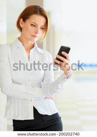 Young busineswoman standing with phone in office lobby