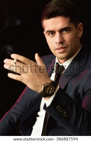 Young busy businessman smoking cigarette at work