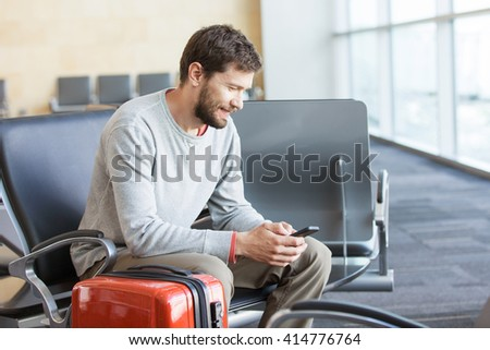 young busy man waiting for departure at the airport while using his phone