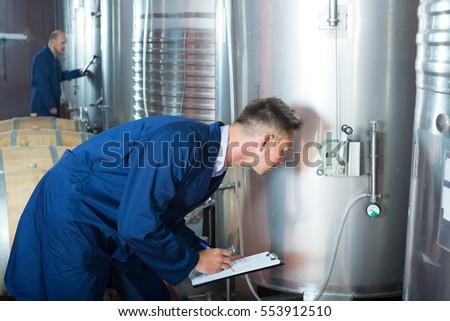 young busy man working in secondary fermenting section on winery and taking notes