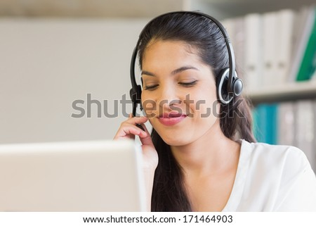Young call center representative using headset in office
