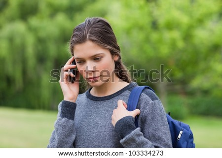 Young calm girl using her cellphone while carrying her backpack