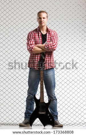 Young, calm musician with electric guitar - stock photo