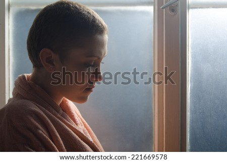 Young cancer patient standing in front of hospital window.