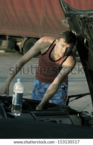 Young car mechanic repairing car engine outdoors