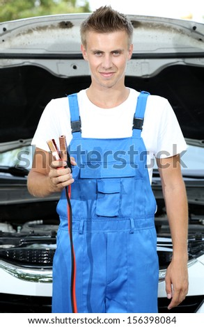 Young car mechanic with battery jumper cables to charge dead battery - stock photo