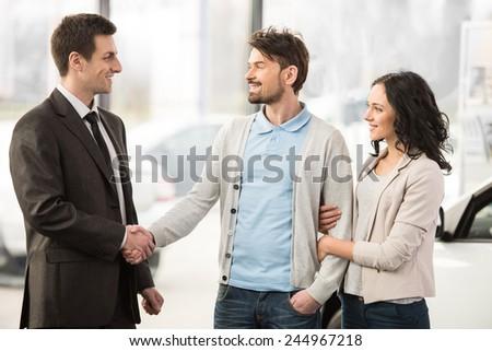 Young car salesman invites customers at showroom. - stock photo