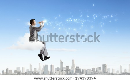 Young carefree businessman sitting on cloud and playing flute - stock photo