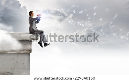 Young carefree businessman sitting on top of building and playing flute - stock photo