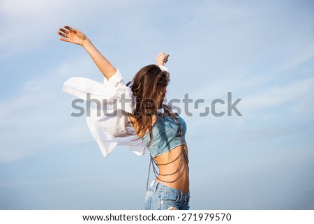 young carefree woman with hands up in blue jeans and white shirt in motion against blue sky  - stock photo