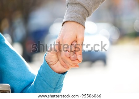 Young Caregiver Holding Senior's Hand Outside - stock photo