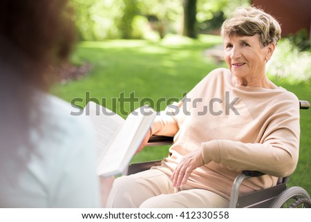 Young caregiver reading a book to senior happy woman - stock photo