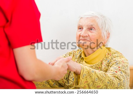 Young carer giving helping hands for the elderly woman - stock photo