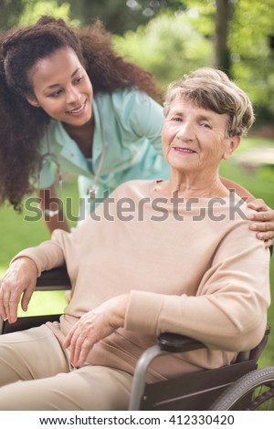 Young caring girl helping to older sick woman - stock photo