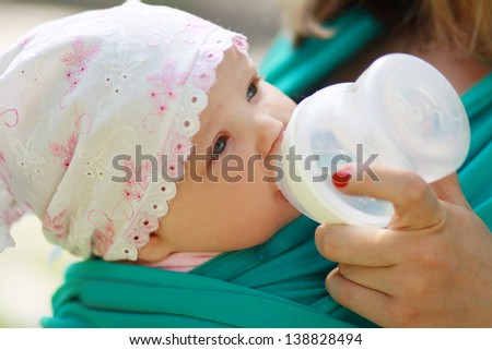 young caring mother gives daughter drink water bottles background summer green park. close up - stock photo