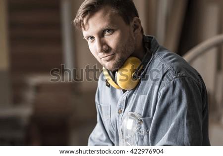 Young carpenter having little break during hard work in carpentry - stock photo