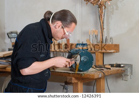 Young carpenter sharpen chisel on grinding machine, sparks fly - stock photo