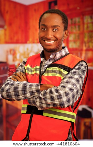 Young carpenter worker wearing square pattern flanel shirt and red safety vest, posing with arms crossed, smiling to camera - stock photo