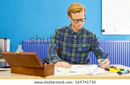 Young cartoonist at work, coloring sketches and drawings behind his desk