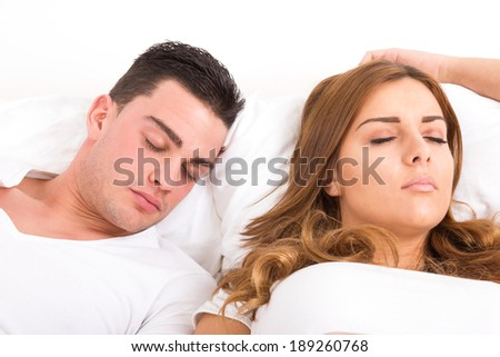 Young casual beautiful couple sleeping in bed, domestic atmosphere