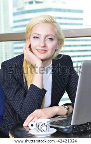 Young casual blond girl indoor, working with laptop