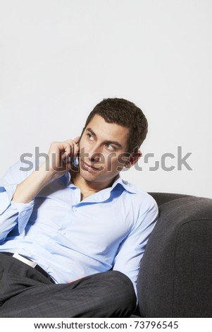 Young casual businessman talking on wireless phone, sitting on sofa relaxing.