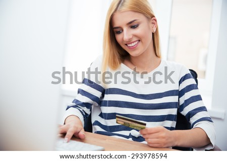 Young casual businesswoman holding bank card and typing on keyboard in office - stock photo