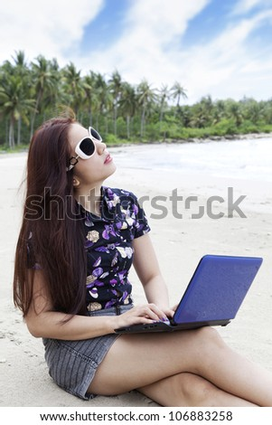Young casual businesswoman using laptop computer at the beach - stock photo