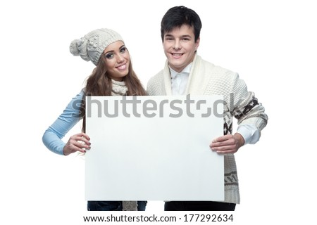 young casual caucasian brunette couple in winter clothing holding big sign and looking at camera with happy smile - stock photo