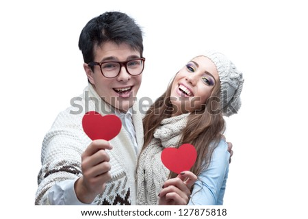 young casual caucasian brunette couple in winter clothing holding red hearts and looking at camera with happy smile - stock photo