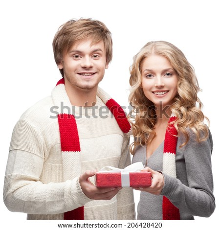 young casual caucasian couple in red scarf holding christmas gift with nice smiles - stock photo