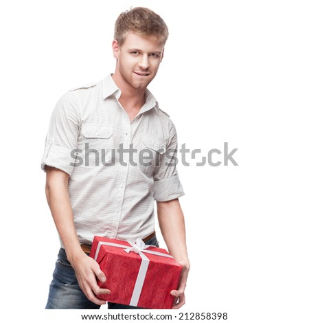 young casual caucasian man holding red christmas gift isolated on white background