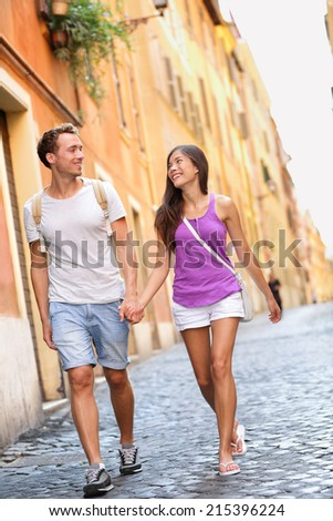 Young casual couple holding hands walking in Rome, Italy, Europe. Multiracial couple in love having fun laughing together. Asian woman, Caucasian man. - stock photo