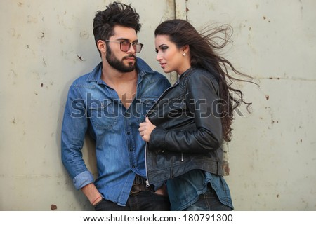 young casual couple posing outdoor, in the wind; the man is holding his hands in his pockets and looking at the woman while she is holding her jacket and looking away - stock photo