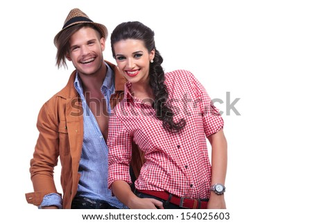 young casual couple smiling for the camera while the man stands behind the woman. on white background