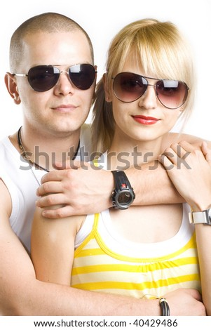young casual couple with sunglasses embraced over white background