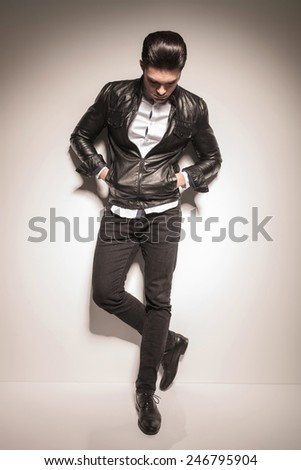 Young casual fashion man looking down with his hands in pockets while leaning on a white wall. - stock photo