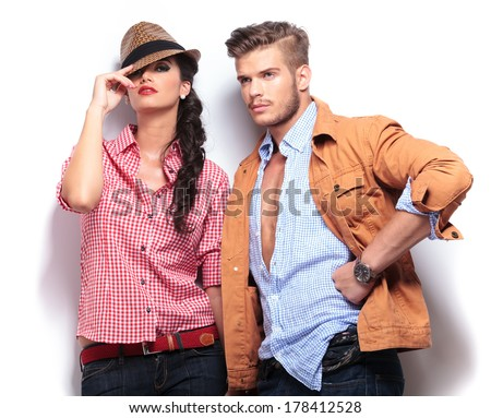 young casual fashion models posing in studio, woman looking at the camaera and man looking away to his side - stock photo