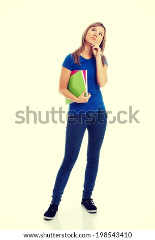 Young casual female student with workbook is thinking.