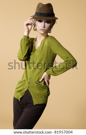 young casual girl in a hat posing on beige background