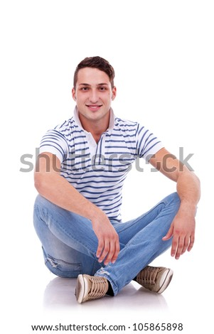 young casual happy man seated on studio, isolated - stock photo