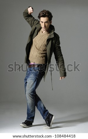 young casual man full body walking over gray background