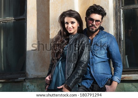 young casual man holding his woman by his side and looking into the camera while she is holding her hands in her pockets and smiling - stock photo