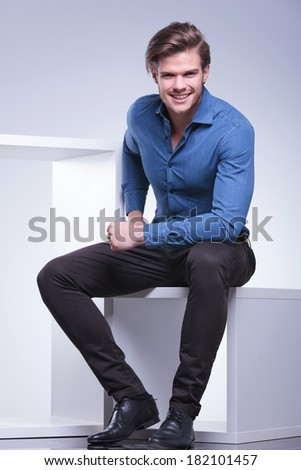 young casual man in shirt and pants is sitting and smiles for the camera, studio shot
