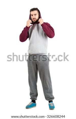 Young casual man in sportswear holding hoodie. Full body length portrait isolated over white studio background. - stock photo