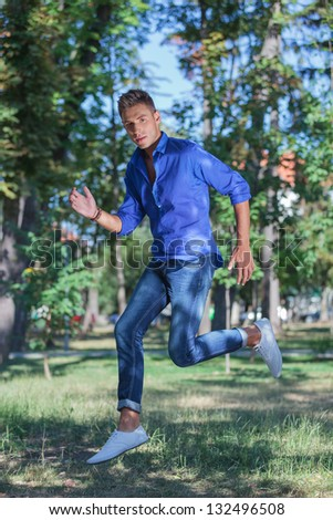 young casual man jumping in the park while looking at the camera