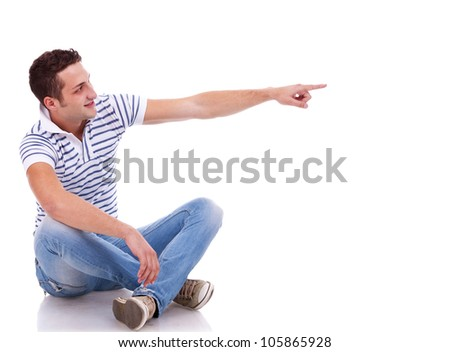 young casual man pointing to his left side on white background - stock photo