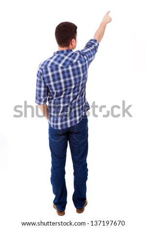 Young casual man pointing towards copyspace, isolated on a white background - stock photo