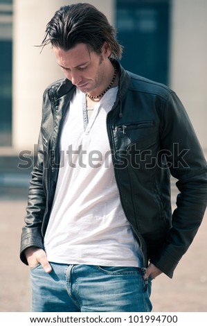 Young casual man portrait with leather jacket outdoors. - stock photo